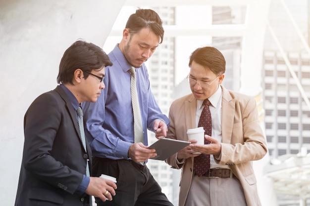 Dojrzały młody biznesmen używa cyfrową pastylkę dyskutować informację