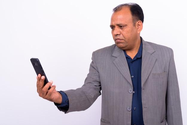 Dojrzały nadwagą indyjski biznesmen w garniturze z cofającą się linią włosów na białym tle