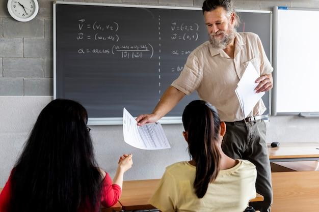 Dojrzały nauczyciel płci męskiej rozdaje kartkę papieru nastolatce uczennicy szkoły średniej edukacja