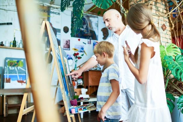 Dojrzały nauczyciel pomaga dzieciom w pracowni artystycznej