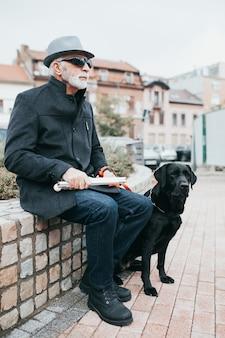 Dojrzały niewidomy z psem przewodnikiem, siedząc na ulicy.