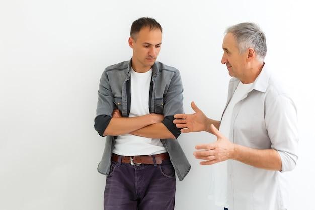 Dojrzały ojciec i syn, kłótnia, na białym tle na białej ścianie