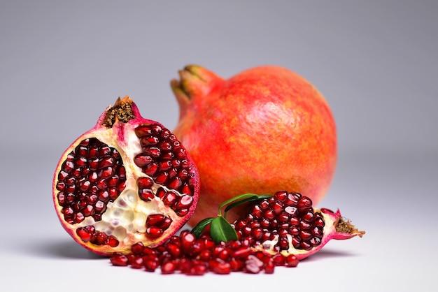Dojrzały owoc granatu i jeden przecięty na pół z liściem na szarym tle