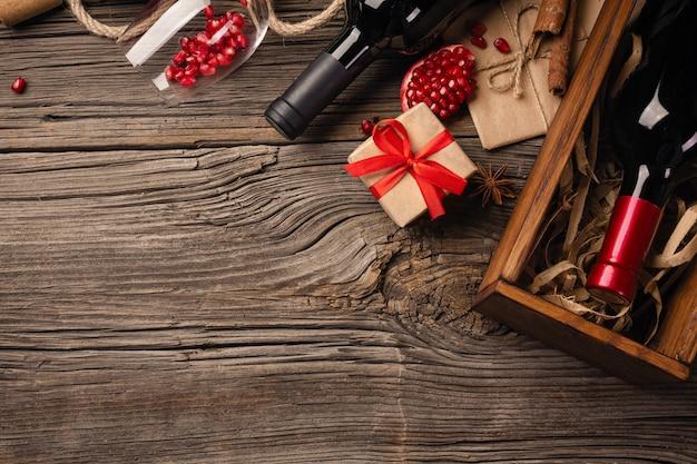 Dojrzały owoc granatu z kieliszek wina, butelki i prezent na drewnianym tle