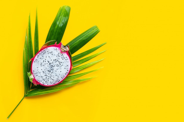 Dojrzały owoc smoka lub pitahaya na tropikalnych liściach palmowych. widok z góry