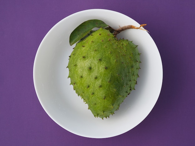 Dojrzały owoc soarsop na białym talerzu, widok z góry.