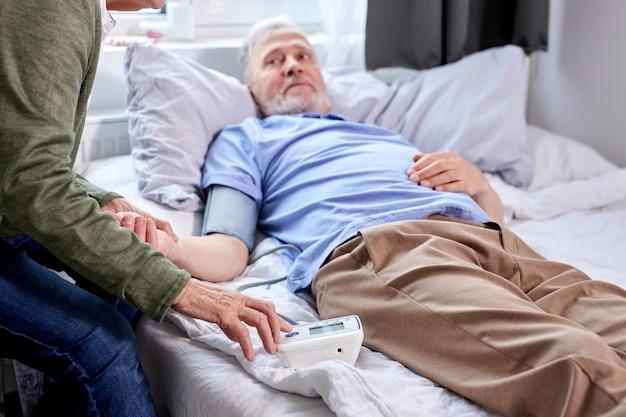 Dojrzały pacjent w szpitalu z zmartwioną żoną siedzącą z nim, sprawdzającą ciśnienie krwi tonometrem. kobieta pomaga, wspiera. skup się na rękach