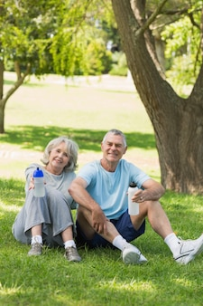 Dojrzały pary obsiadanie z bidonami przy parkiem