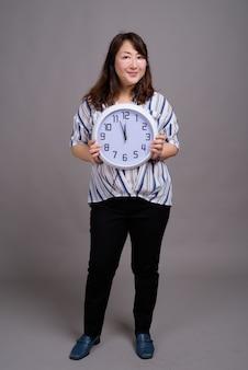 Dojrzały piękny azjatycki bizneswoman gospodarstwa zegar