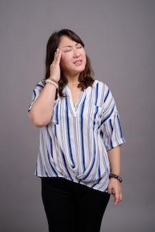 Dojrzały piękny azjatycki bizneswoman z bólem głowy