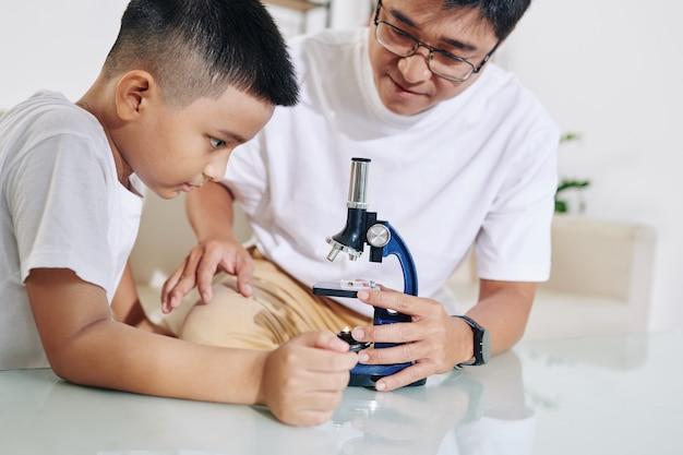 Dojrzały, poważny ojciec wyjaśnia synowi preteen, jak używać mikroskopu