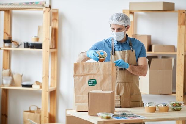 Dojrzały pracownik płci męskiej ubrany w odzież ochronną podczas bezpiecznego pakowania zamówień przy drewnianym stole w usłudze dostarczania żywności