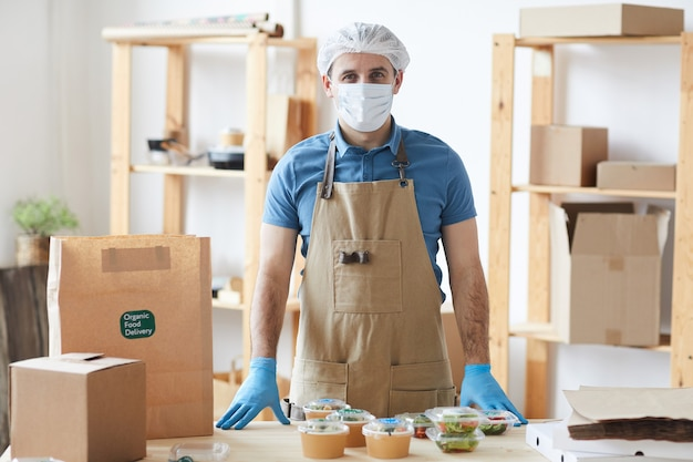 Dojrzały pracownik ubrany w odzież ochronną podczas bezpiecznego pakowania zamówień przy drewnianym stole w usłudze dostawy żywności