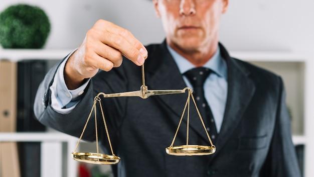 Dojrzały prawnik trzyma złotą skala sprawiedliwość w ręce