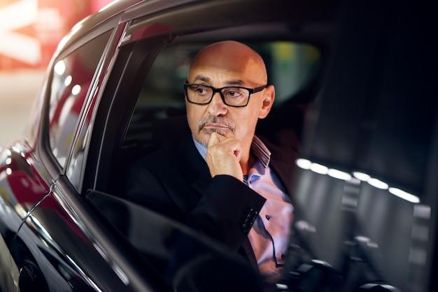 Dojrzały profesjonalista, zaniepokojony sukcesem biznesmen, jedzie na tylne siedzenie samochodu, patrząc przez okno.