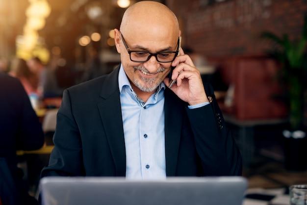 Dojrzały profesjonalny radosny biznesmen używa laptop i telefon w kawiarni