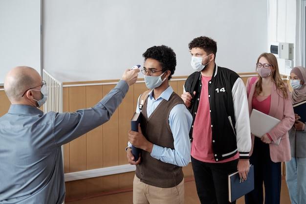 Dojrzały profesor mierzący temperaturę uczniów przed lekcją