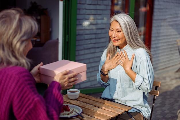 Dojrzały przyjaciel daje prezent emocjonalnej azjatyckiej kobiecie siedzącej przy małym stoliku w kawiarni