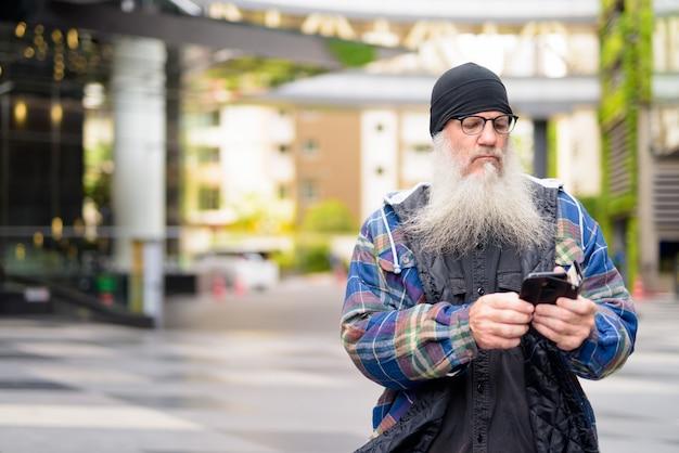 Dojrzały przystojny brodaty mężczyzna za pomocą telefonu na ulicach miasta na zewnątrz