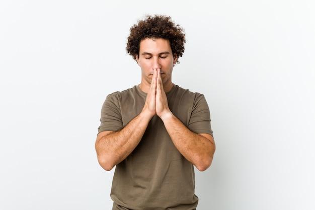 Dojrzały przystojny mężczyzna na białym tle trzymając się za ręce modlić się w pobliżu ust, czuje się pewnie.