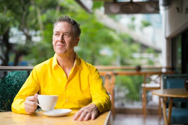 Dojrzały przystojny mężczyzna siedzi w kawiarni i myśli