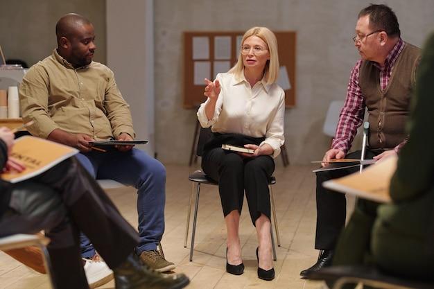 Dojrzały psycholog rozmawia z grupą osób podczas sesji