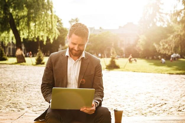 Dojrzały radosny mężczyzna w szarym klasycznym garniturze, siedząc w parku z kawą na wynos podczas pracy na srebrnym laptopie