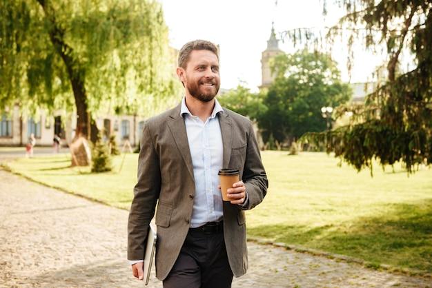 Dojrzały radosny mężczyzna w szarym klasycznym garniturze, spacerujący po parku z kawą na wynos i srebrnym laptopem
