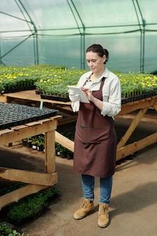 Dojrzały rolnik korzystający z tabletu stojąc przy jednym ze stołów z sadzonkami