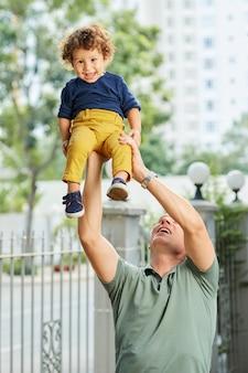 Dojrzały silny mężczyzna podnosi małego syna nad głowę, gdy bawią się razem na świeżym powietrzu