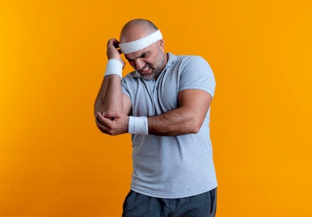 Dojrzały sportowy mężczyzna w opasce dotykając łokcia, patrząc źle czuje ból stojąc nad pomarańczową ścianą