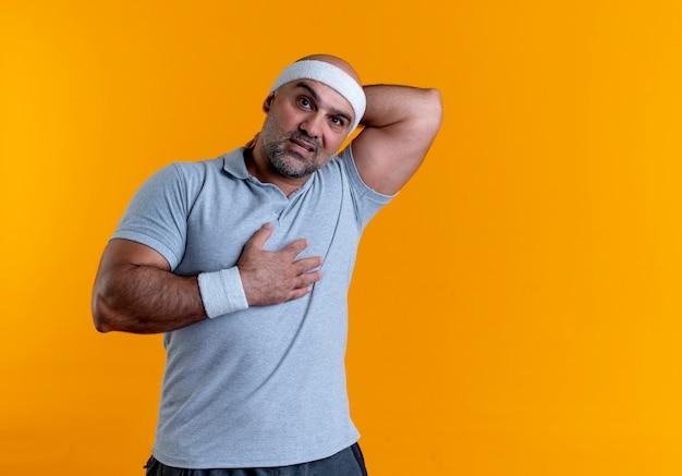Dojrzały sportowy mężczyzna w opasce patrząc do przodu, dotykając jego szyi, patrząc zdezorientowany stojąc nad pomarańczową ścianą