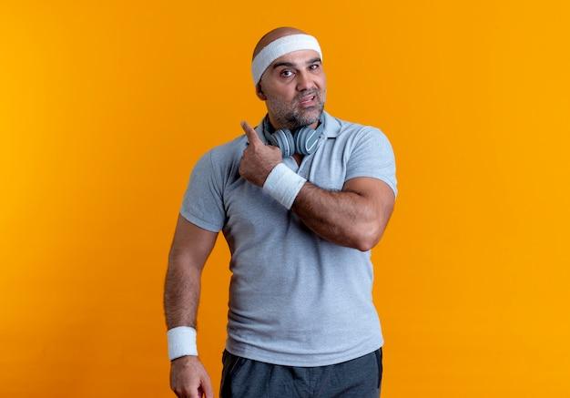 Dojrzały sportowy mężczyzna w opasce patrząc do przodu ze zdezorientowanym wyrazem wskazującym do tyłu stojąc na pomarańczowej ścianie