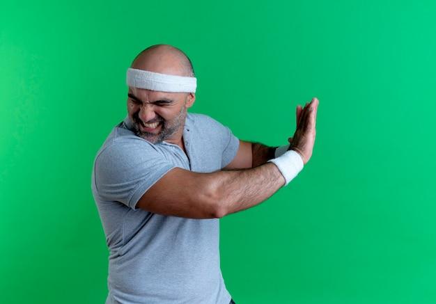 Dojrzały sportowy mężczyzna w opasce robi gest obrony rękami z obrzydzonym wyrazem stojącym nad zieloną ścianą