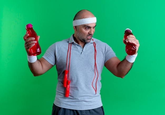 Dojrzały sportowy mężczyzna w opasce trzyma butelki wody patrząc zdezorientowany stojąc nad zieloną ścianą
