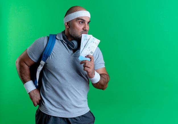 Dojrzały sportowy mężczyzna w opasce trzyma dwa bilety lotnicze patrząc na bok zdziwiony stojąc nad zieloną ścianą