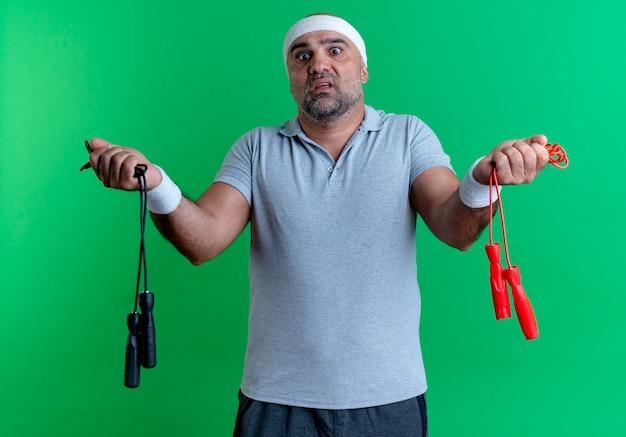Dojrzały sportowy mężczyzna w opasce trzyma dwie skaczące liny patrząc na nich zdezorientowany, mając wątpliwości stojąc nad zieloną ścianą