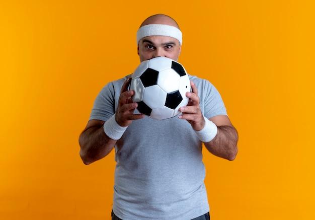 Dojrzały sportowy mężczyzna w opasce trzyma piłkę nożną patrząc do przodu stojący nad pomarańczową ścianą