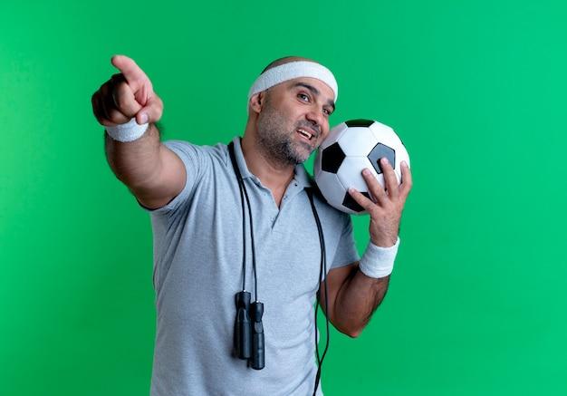 Dojrzały sportowy mężczyzna w opasce trzyma piłkę nożną patrząc do przodu, uśmiechając się radośnie, wskazując palcem do przodu, stojąc nad zieloną ścianą