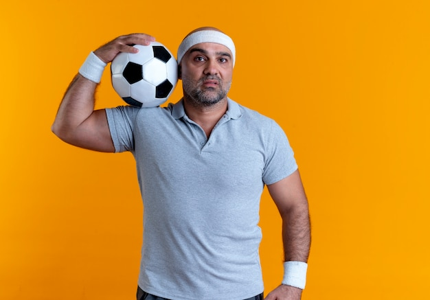 Dojrzały sportowy mężczyzna w opasce trzyma piłkę nożną patrząc do przodu z poważną twarzą stojącą nad pomarańczową ścianą