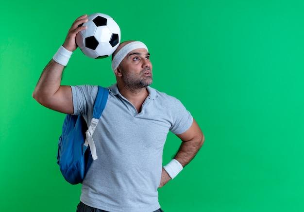 Dojrzały sportowy mężczyzna w opasce trzyma piłkę nożną patrząc na bok zdziwiony stojący nad zieloną ścianą