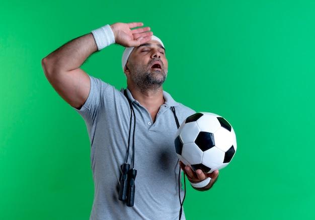 Dojrzały sportowy mężczyzna w opasce trzyma piłkę nożną patrząc zmęczony i wyczerpany po treningu stojąc nad zieloną ścianą