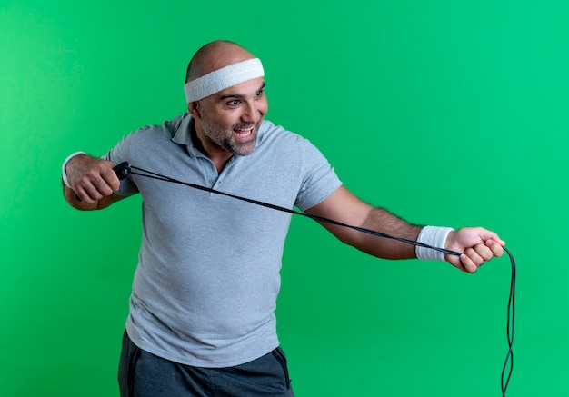 Dojrzały sportowy mężczyzna w opasce trzyma skakankę patrząc na bok, uśmiechając się wesoło stojąc na zielonej ścianie