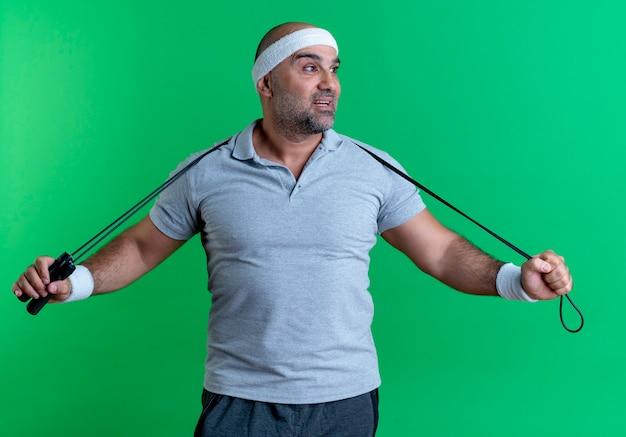 Dojrzały sportowy mężczyzna w opasce trzyma skakankę patrząc na bok z uśmiechem na twarzy stojącej nad zieloną ścianą