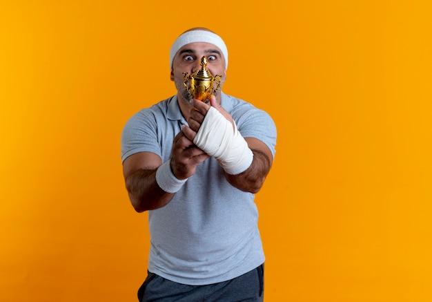Dojrzały sportowy mężczyzna w opasce trzyma trofeum patrząc zaskoczony i zdumiony stojąc nad pomarańczową ścianą