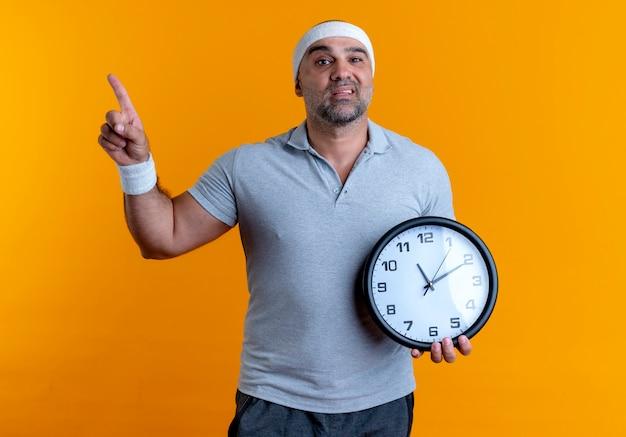 Dojrzały sportowy mężczyzna w opasce trzyma zegar ścienny, wskazując palcem w bok, patrząc zdezorientowany stojąc na pomarańczowej ścianie