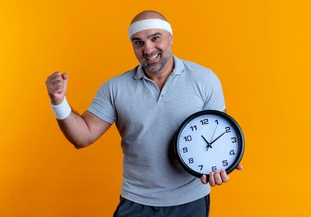 Dojrzały sportowy mężczyzna w opasce trzyma zegar ścienny zaciskając pięść szczęśliwy i podekscytowany stojąc nad pomarańczową ścianą