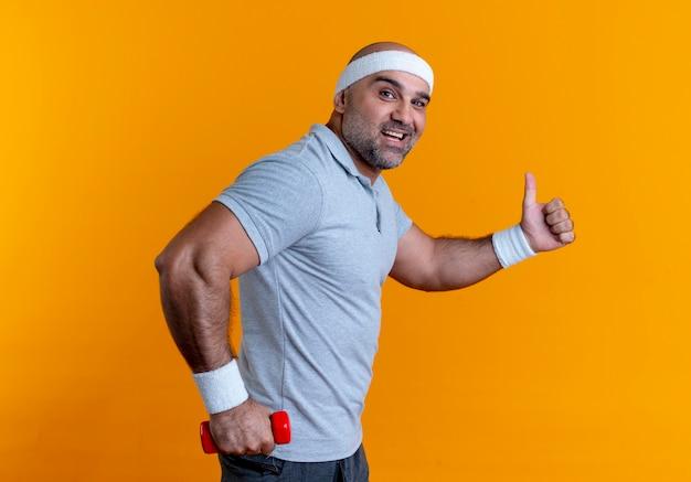Dojrzały sportowy mężczyzna w opasce trzymając hantle patrząc do przodu uśmiechnięty radośnie pokazując kciuki do góry stojąc na pomarańczowej ścianie