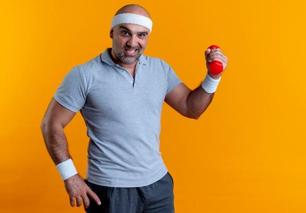Dojrzały sportowy mężczyzna w opasce, trzymając hantle pewnie robi ćwiczenia stojąc nad pomarańczową ścianą