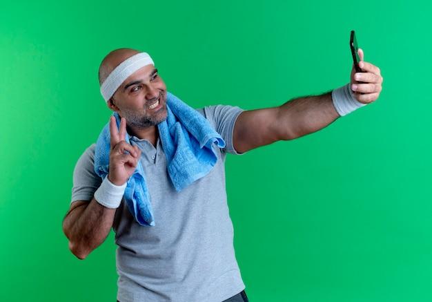 Dojrzały sportowy mężczyzna w opasce z ręcznikiem na szyi, biorąc selfie za pomocą smartfona, uśmiechając się, pokazując znak zwycięstwa stojący nad zieloną ścianą
